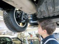 Mechaniker unterm Fahrzeug checkt die Reifengröße